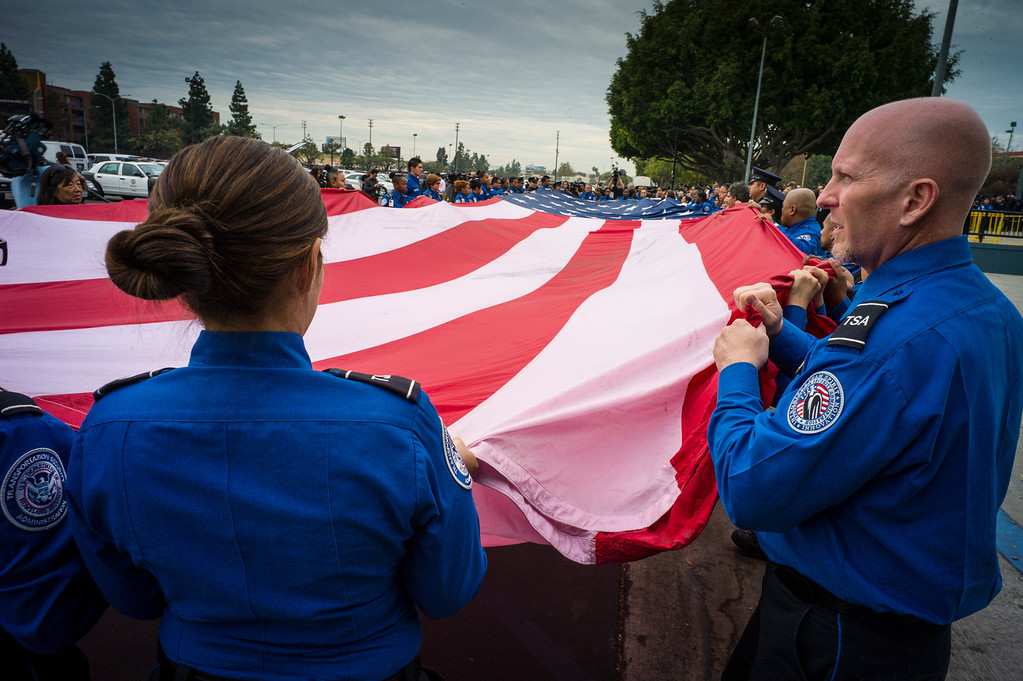 Description of . TSA officers fold a giant US flag at the memorial for slain TSA officer Gerardo Hernandez at the Los Angeles Sports Arena Tuesday, November 12, 2013.  A public memorial was held for Officer Gerardo who was killed at LAX when a gunman entered terminal 3 and opened fire with a semi-automatic rifle.  ( Photo by David Crane/Los Angeles Daily News )