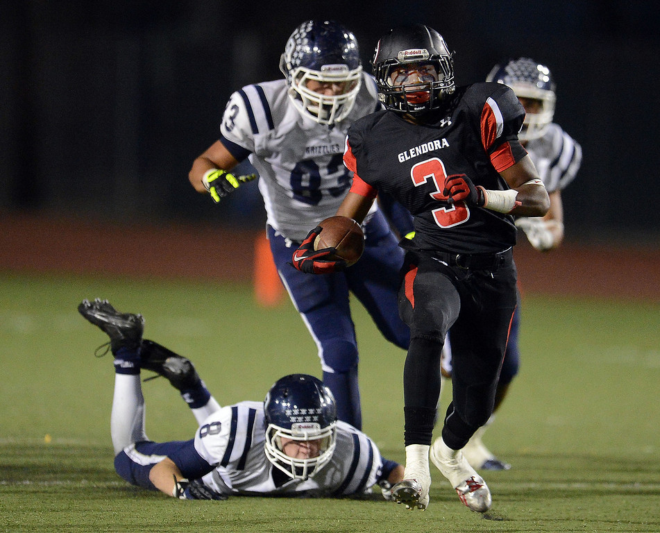 Description of . Glendora's TyRell Evans (3) runs for a first down past the diving Los Osos' Tyler Lyon (8) in the first half of a prep football game at Citrus College in Glendora, Calif., on Thursday, Oct. 31, 2013.    (Keith Birmingham Pasadena Star-News)