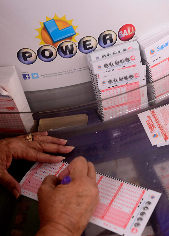 Description of . Gloria Ybarra, of Fontana, picks numbers on a Powerball ticket at Quicker Liquor along Sierra Avenue in Fontana May 17, 2013.  The Powerball Lottery, which California just joined earlier this year, is at $600 million for Saturday's drawing.  It is the third-highest jackpot in U.S. history.  GABRIEL LUIS ACOSTA/STAFF PHOTOGRAPHER.