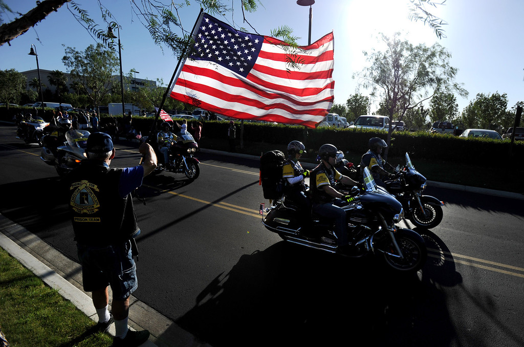 Description of . Navy veteran Jerry Bayless of Westminster, holds the U.S. flag as Run For The Wall (RFTW) riders leave Rancho Cucamonga, Wednesday morning from Victoria Gardens, heading to the Vietnam Memorial Wall in Washington D.C., May 14, 2014. (Photo by John Valenzuela/Inland Valley Daily Bulletin)
