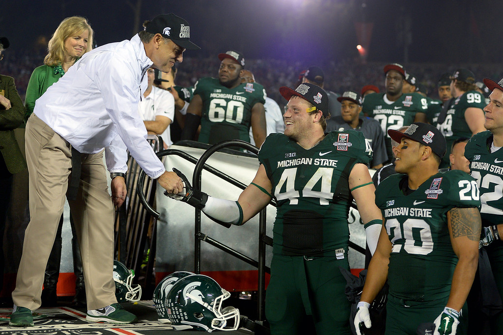Description of . Michigan State head coach Mark Dantonio shakes hands with his team during the trophy presentation after beating Stanford 24-20 at the Rose Bowl, Wednesday, January 1, 2014. (Photo by Michael Owen Baker/L.A. Daily News)