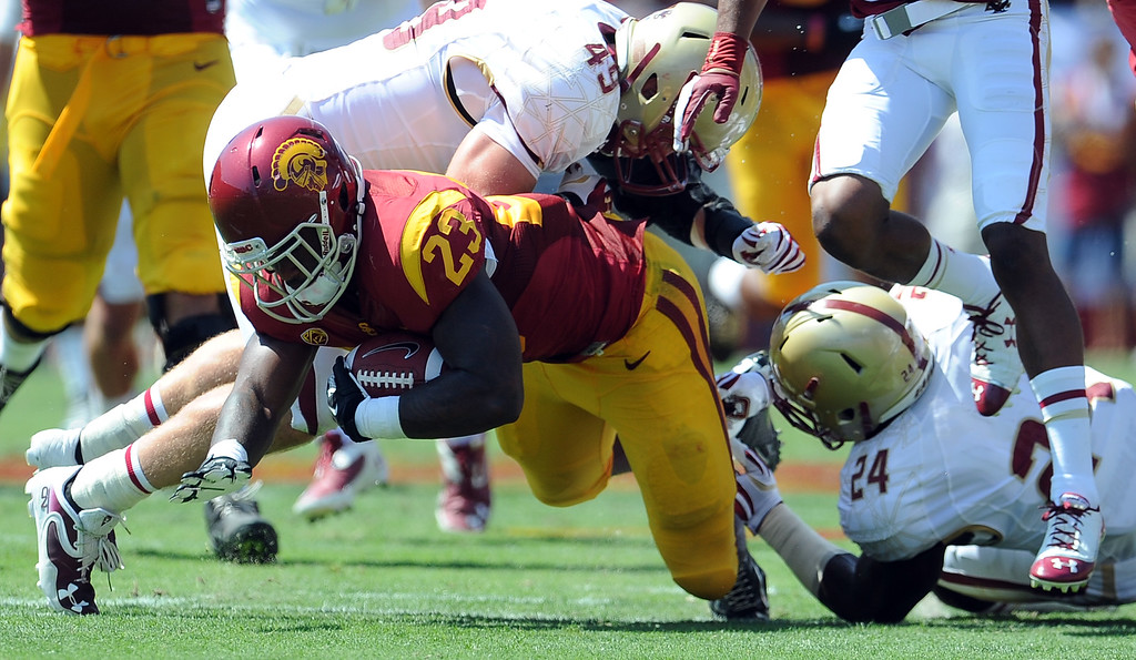 Description of . Southern California running back Tre Madden (23) runs for a sixteen yard first down against Boston College during the first half of an NCAA college football game in the Los Angeles Memorial Coliseum in Los Angeles, on Saturday, Sept. 14, 2013.