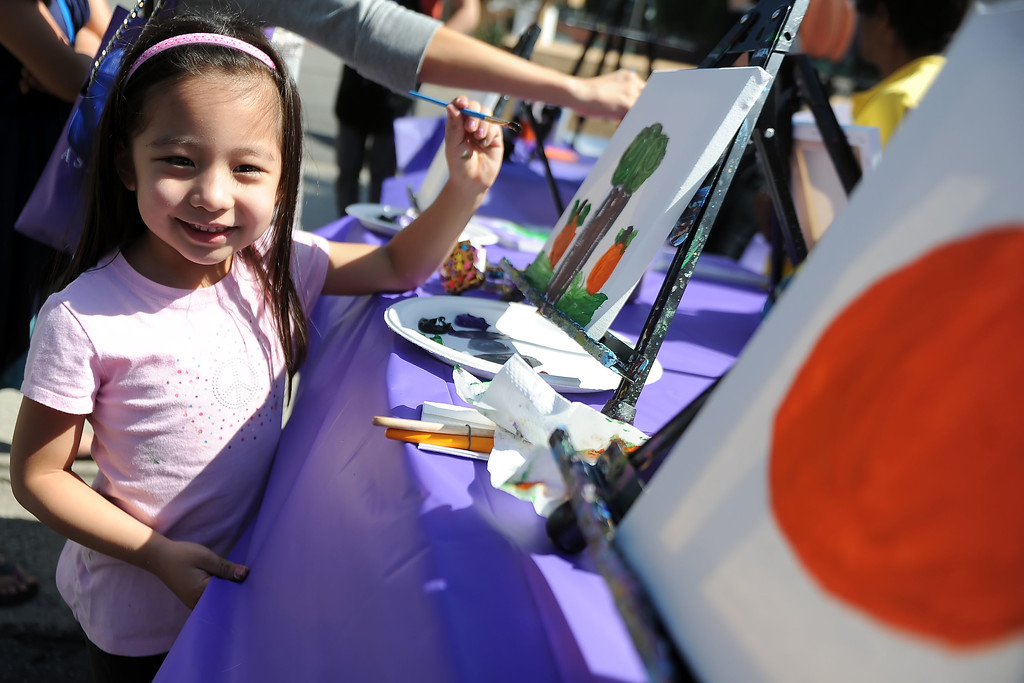 Description of . Five year-old Makayla Gatmaitan of Altadena smiles as she paints during the 8th Annual Pasadena ARTWalk along El Molino Avenue between Colorado Boulevard and Green Street in Pasadena, Calif., on Saturday, Oct. 12, 2013. The ArtWalk features over 30 participating artists, art sales, gallery walks, musical performances and other activities.   (Keith Birmingham Pasadena Star-News)