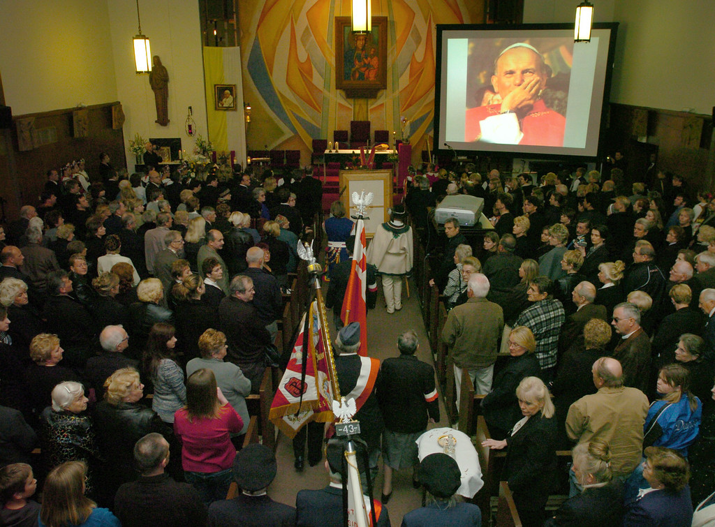 Description of . 4/7/05--Los Angeles CA--The Parish at Our Lady of the Bright Mount Church rises to its feet while a procession enters. A slide show featuring images of Pope John Paul II is projected in the corner of the church. (John McCoy/Los Angeles Daily News file photo)