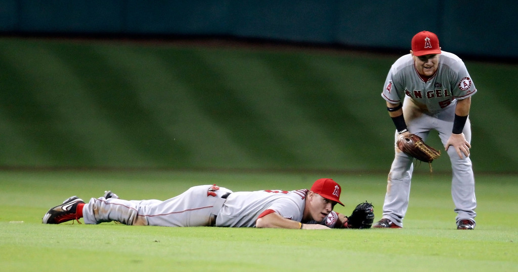Description of . Los Angeles Angels' Mike Trout, left, reacts to missing a shallow fly ball as Kole Calhoun stands next to him during the seventh inning of a baseball game against the Houston Astros Saturday, Sept. 14, 2013, in Houston. (AP Photo/Eric Christian Smith)