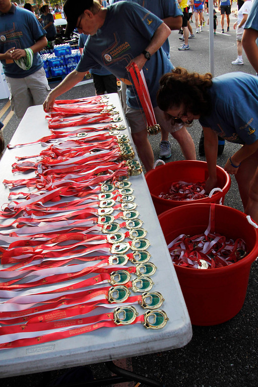 Description of . Organizers prepare the 5k medals for the participants, during the 5th Annual Pasadena Marathon Event, at Pasadena City College, in Pasadena, Sunday, June 30, 2013. (SXCITY/Correspondent Photo by James Carbone)