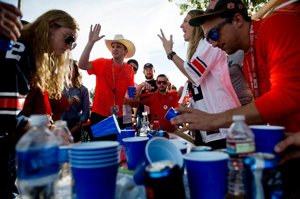 Description of . Auburn fans play a game of flip cup during the tailgate party before the BCS National Championship game at the Rose Bowl in Pasadena Calif. on Monday, Jan. 6, 2014. (Watchara Phomicinda/ Pasadena Star-News)