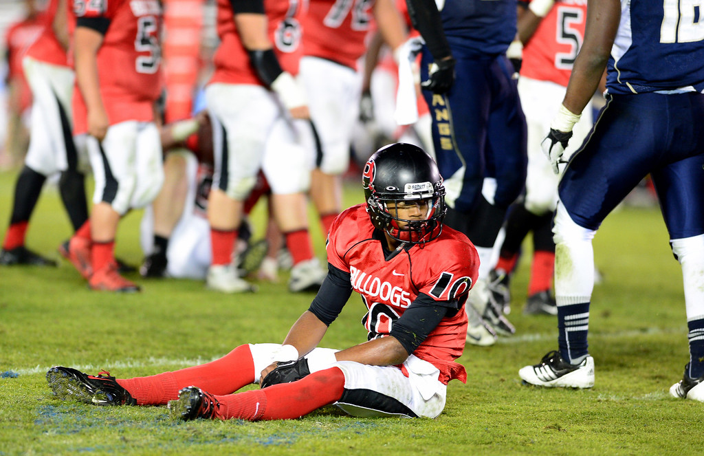 Description of . Pasadena's Xavier Hill (10) is taken down in the fourth quarter during the annual Turkey Tussle Friday night, November 8, 2013 at the Rose Bowl in Pasadena. Muir defeated Pasadena 32-21.(Photo by Sarah Reingewirtz/Pasadena Star-News)