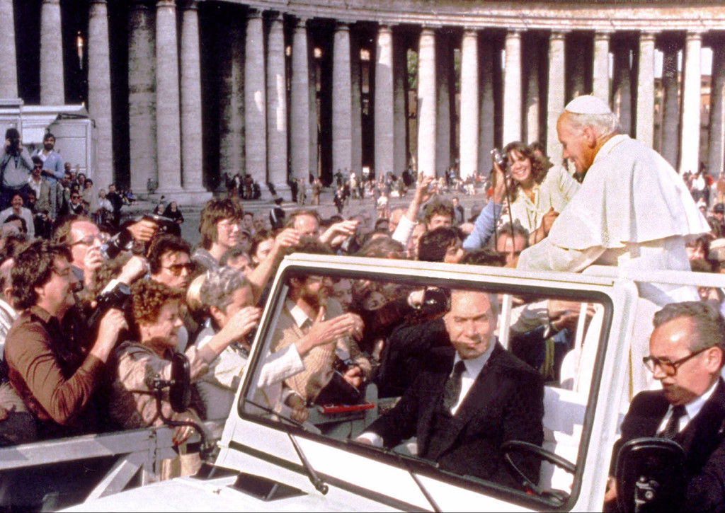 Description of . A hand holding a pistol, left, aims from the crowd at Pope John Paul II in St. Peter's Square in Rome in this May 13, 1981 file photo. (AP Photo, File)