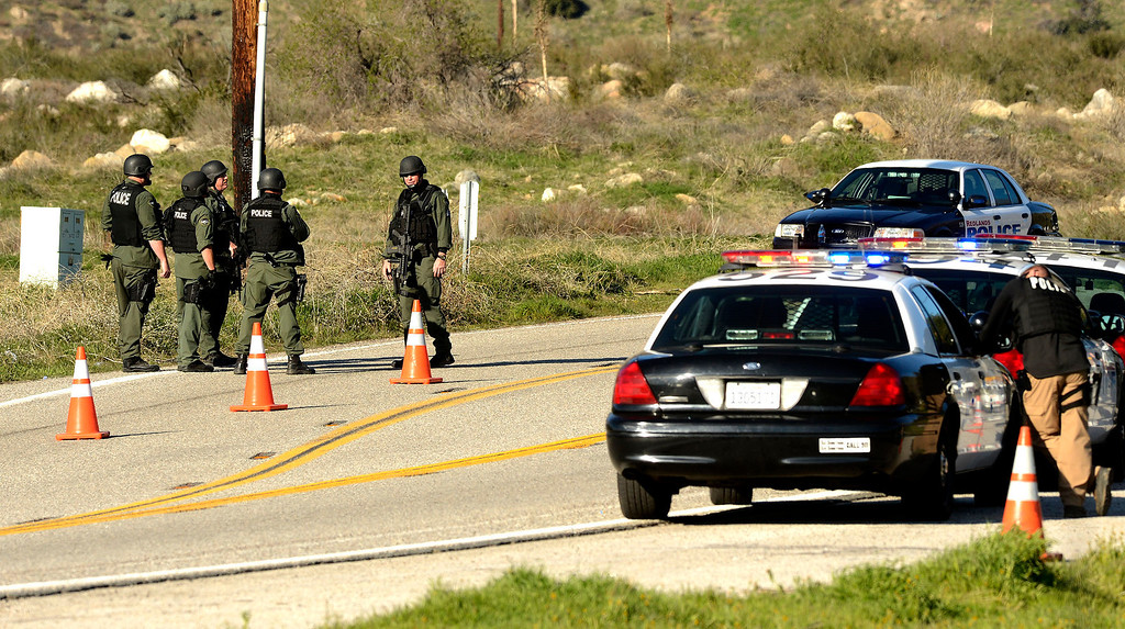 Description of . A SWAT team stands guard at a blockade at Highway 38 and Bryant Street near the Mill Street Ranger Station west of Yucaipa February 12, 2013.   Authorities exchanged gunfire with fugitive Christopher Dorner in the Angles Oaks area of the San Bernardino National Forest.  Fish and Game officers spotted a man fitting the description of Dorner and exchanged gunfire with him. (Staff photo by Gabriel Luis Acosta/The Sun)