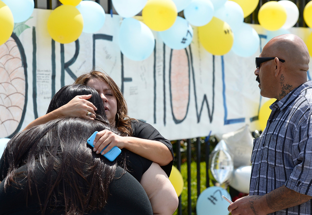 Description of . Jessica,27, gets a hug from her mother Aida as David De La Cruz looks on. The family are friends of the Castro family. Students at El Monte High School brought flowers, candles and other items in remembering Adrian Castro, a Senior student who was killed in bus crash in Northern California that took the lives of 10 people. El Monte, CA. 4/13/2014(Photo by John McCoy / Los Angeles Daily News)