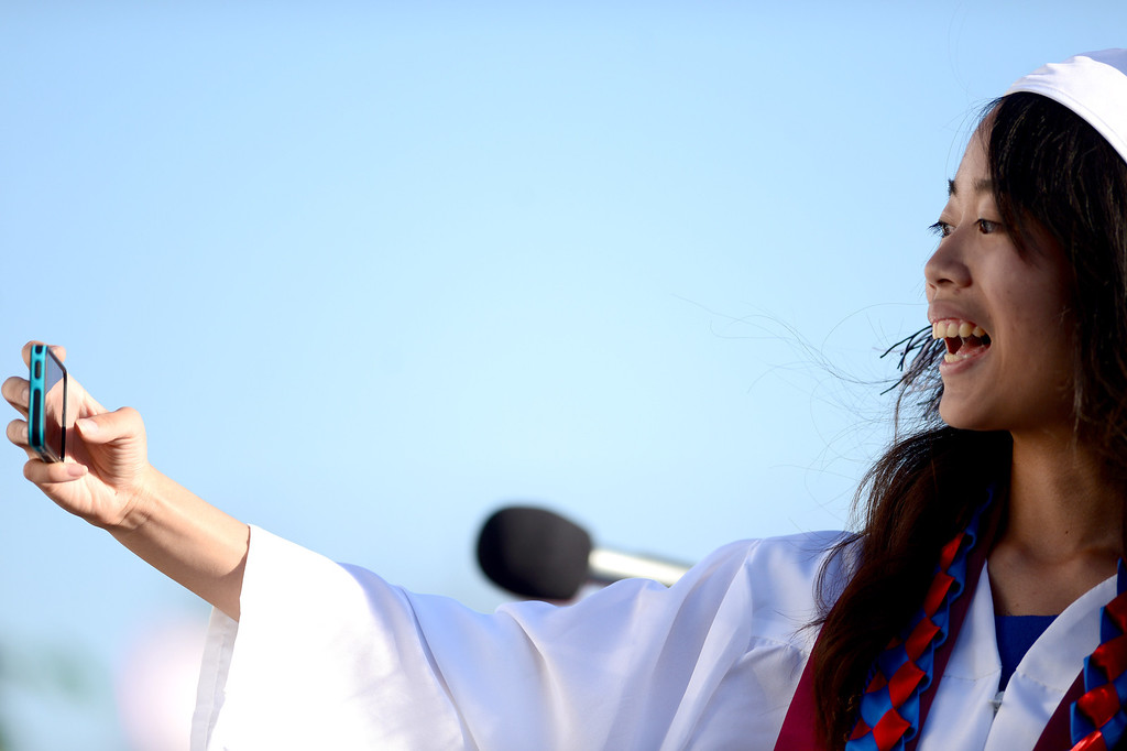 Description of . Yun-Ju Chen takes a selfie before giving the valedictory address during Duarte High School's commencement ceremony Thursday night,  June 12, 2014 at the Duarte school. (Photo by Sarah Reingewirtz/Pasadena Star-News)