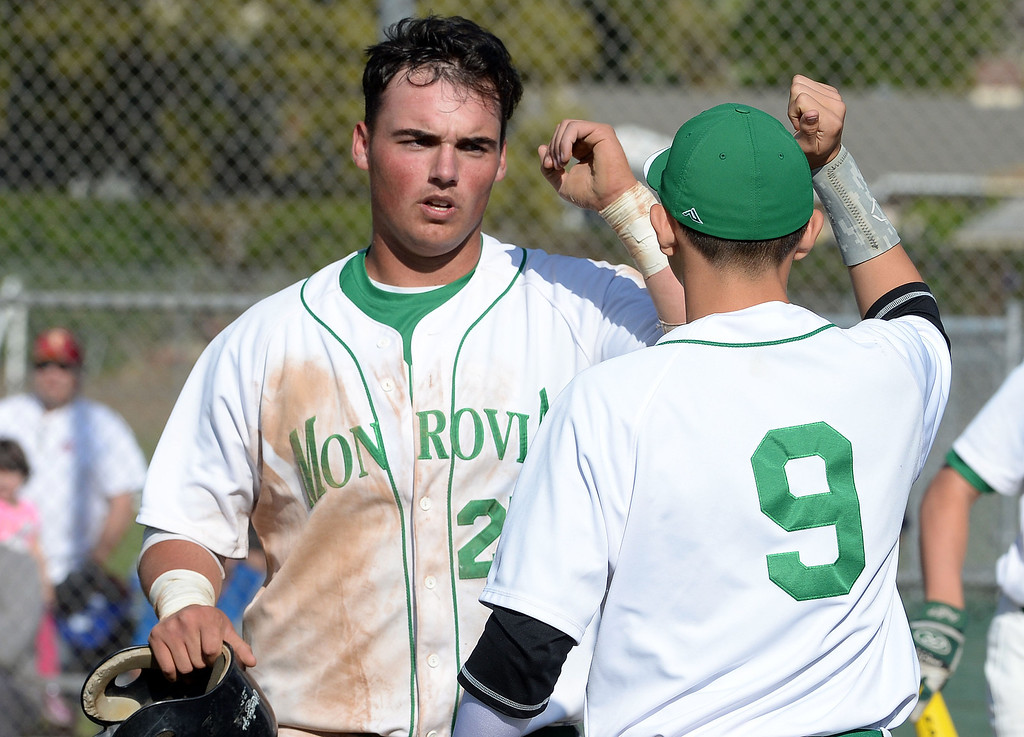 Description of . Monrovia's Jason Daly (25) high fives teammate Isaiah Ramos (9) after scoring in the fourth inning of the Arcadia Elk Baseball Tournament against Alhambra at Monrovia High School in Monrovia, Calif., on Thursday, March 13, 2014. Monrovia won 2-0.  (Keith Birmingham Pasadena Star-News)