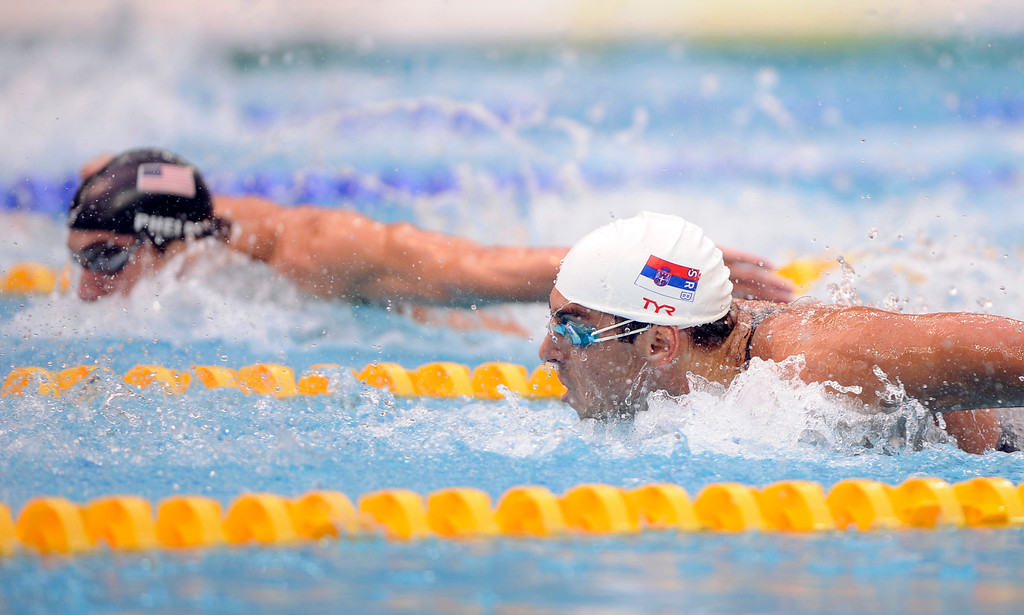 Description of . United States\' Michael Phelps, left, leads in front of Serbia\'s Milorad Cavic during the the 100-meter butterfly final at swimming competitions in the National Aquatics Center at the Beijing 2008 Olympics in Beijing, Saturday, Aug. 16, 2008. Phelps won the gold. (AP Photo/Mark J. Terrill)