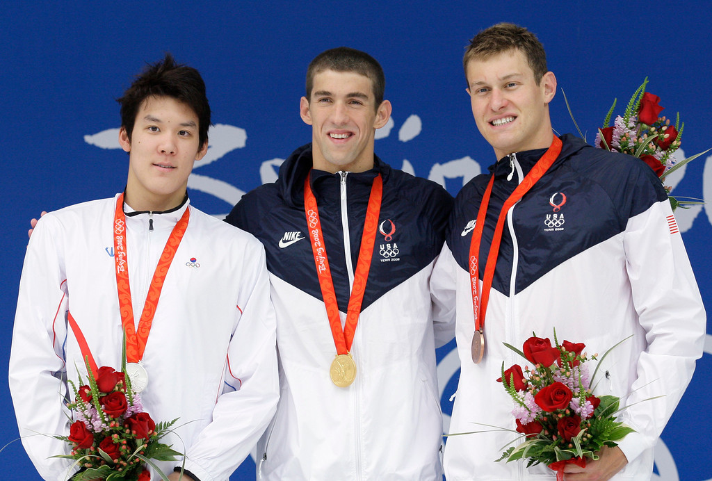 Description of . United States\' gold medal winner Michael Phelps, center, is flanked by  South Korea\'s silver medalist Park Tae-hwan, left, and  United States\' bronze medal winner Peter Vanderkaay at the medal ceremony of the men\'s 200-meter freestyle final during the swimming competitions in the National Aquatics Center at the Beijing 2008 Olympics in Beijing, Tuesday, Aug. 12, 2008. (AP Photo/David J. Phillip)
