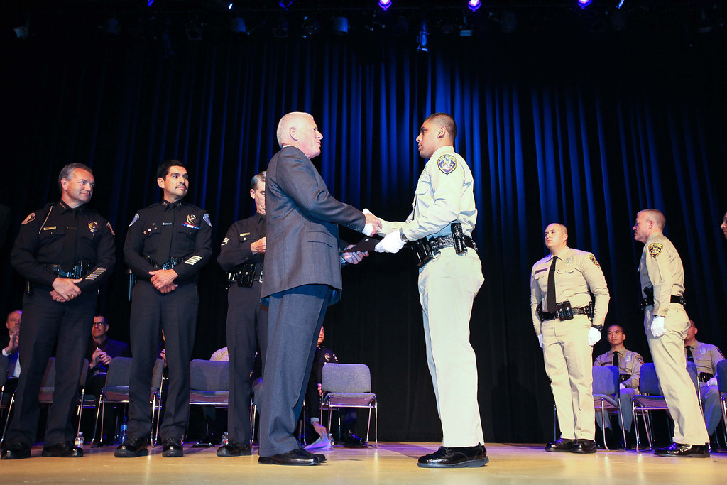 Description of . Retired Gilroy Assistant Police Chief Lanny Brown congratulates Rio Hondo Police Academy graduate Felix Andrez. Rio Hondo celebrated their first Police Academy graduation since closing in 2010, Saturday morning July 13, 2013, at the Rio Hondo College Wray Theatre. (Correspondent photo by Chris Burt)