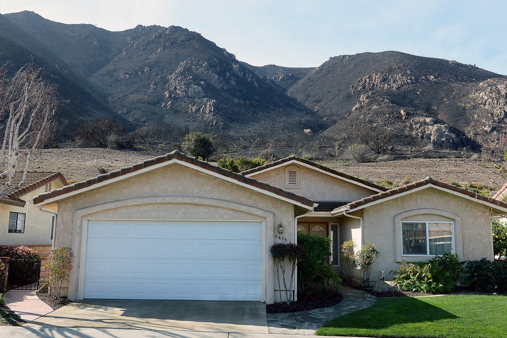 Description of . A home in Camarillo Springs abuts against a burnt hillside from last year's Springs Fire, Thursday, February 27, 2014. (Photo by Michael Owen Baker/L.A. Daily News)