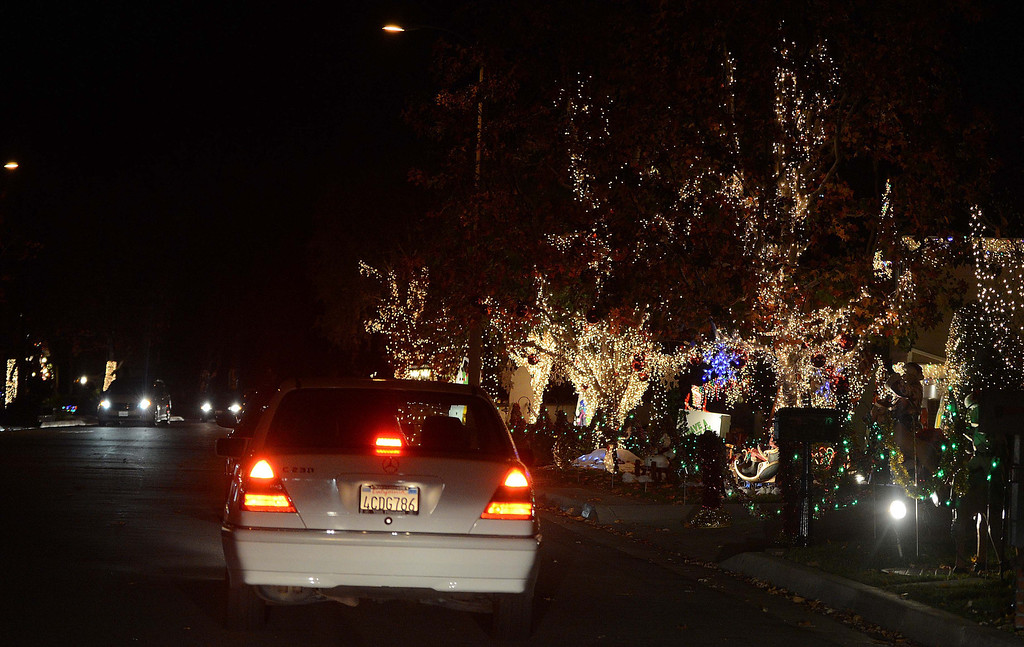 Description of . Rancho Cucamonga residents put their Christmas lights up along Thoroughbred Street for show Thursday night December 5, 2013 in Rancho Cucamonga. LaFonzo Carter/ Staff Photographer