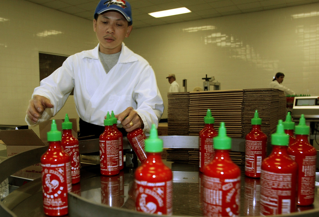Description of . Hang Sy collects bottles of 'Sriracha' hot sauce during the packing phase of production Friday January 28th 2005 at Huy Fong Foods Inc. in Rosemead. (BUSINESS/staff photo by Greg Andersen)