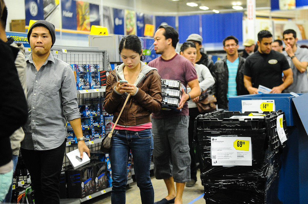 Description of . Shoppers wait in a very long line at Best Buy after the store opened its doors at 6 p.m. for early Black Friday sales on Thanksgiving in San Bernardino on Thursday, Nov. 28, 2013. Many retail stores pushed the boundary the Black Friday tradition this year with offering Black Friday deals on Thanksgiving day. (Photo by Rachel Luna / San Bernardino Sun)