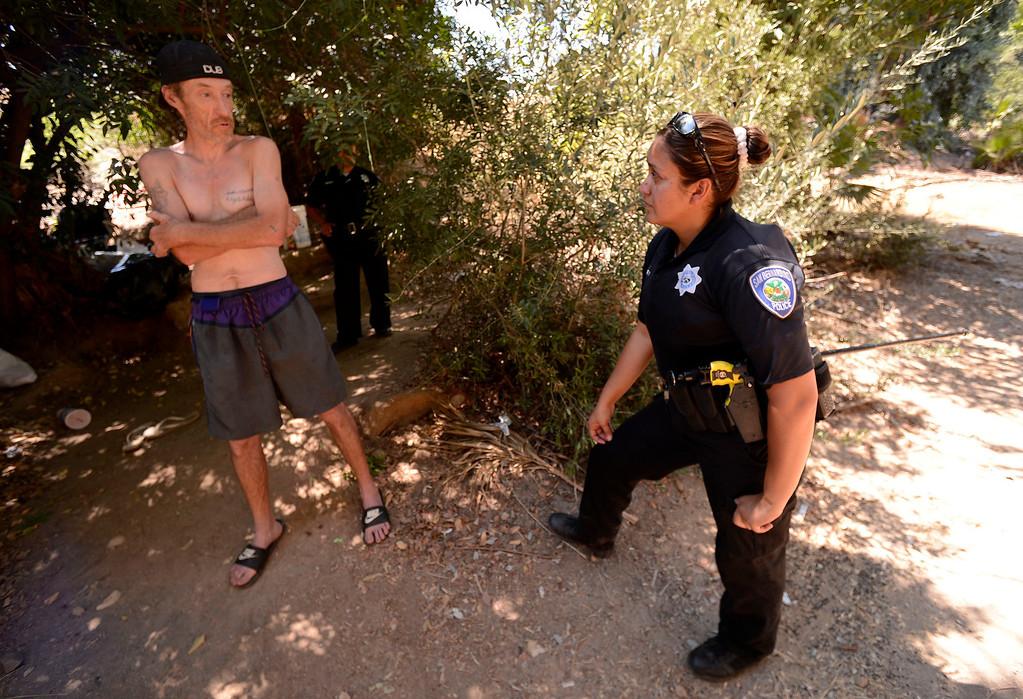 Description of . San Bernardino Police Officer Sochilt Martinez, right,  questions Anthony Ethridge, 45, whose been living along the I-210 freeway in San Bernardino August 14, 2013. GABREL LUIS ACOSTA/STAFF PHOTOGRAPHER.