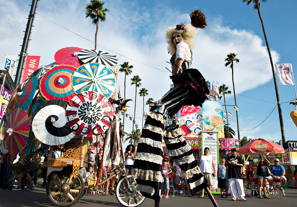 Description of . A performer walks on stilts in a parade during the opening day of L.A. County Fair in Pomona on Friday, Aug. 30, 2013. (Staff photo by Watchara Phomicinda/ San Gabriel Valley Tribune)