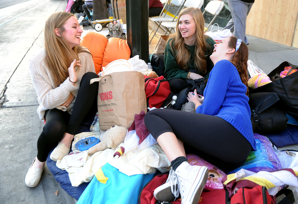 Description of . Hope Freeman, left, along with Elle Kenwood, center, and Stephanie Beck of La Canada stake out their spots for the Rose Parade along Colorado Boulevard in Pasadena, Calif., on Tuesday, Dec. 29, 2013.     (Keith Birmingham Pasadena Star-News)