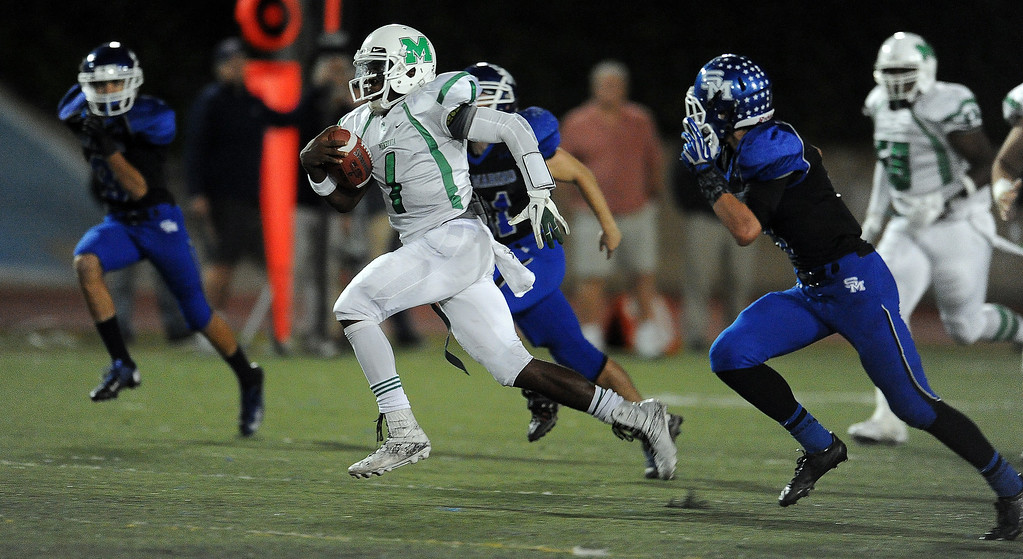 Description of . Monrovia quarterback Deshawn Potts (C) (1) runs for a first down against San Marino in the first half of a prep football game at Monrovia High School in Monrovia, Calif., on Friday, Nov. 8, 2013. 