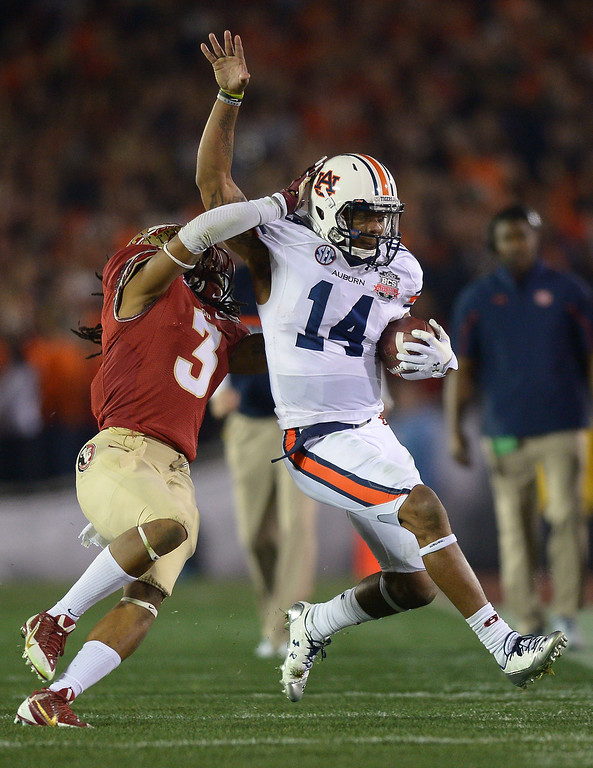 Description of . Auburn QB Nick Marshall is hit by Florida State's Ronald Darby in the second quarter at the BCS national championship game at the Rose Bowl, Monday, January 6, 2014. (Photo by Michael Owen Baker/L.A. Daily News)