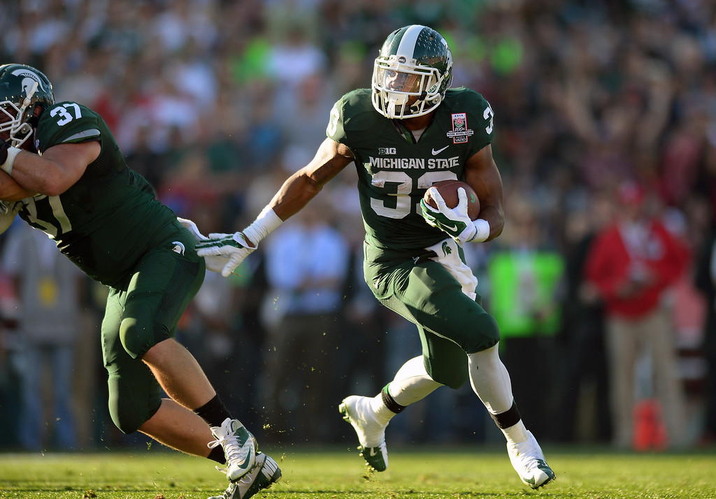 Description of . Michigan State RB Jeremy Langford follows blocker Trevon Pendleton and goes in for a two-yard touchdown in the second quarter against Stanford at the Rose Bowl, Wednesday, January 1, 2014. (Photo by Michael Owen Baker/L.A. Daily News)