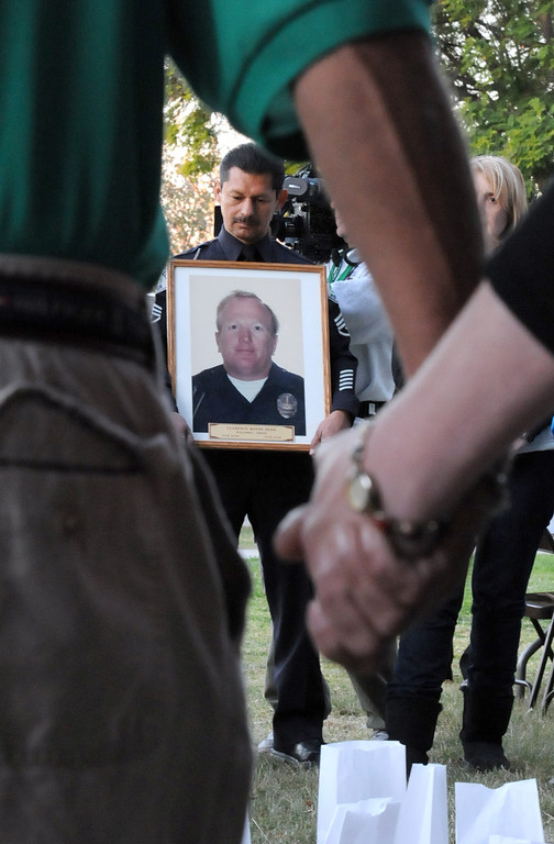 Description of . LAPD Detective, William Bustos holds a photo of Officer Wayne Clarence Dean, who was killed on his way to aid in rescue efforts following the Northridge earthquake.  Bustos shared stories of his colleague during the program. Councilman Mitch Englander, other officials and residents recalled the 1994 Northridge earthquake, 20 years later, by lighting luminaries and sharing