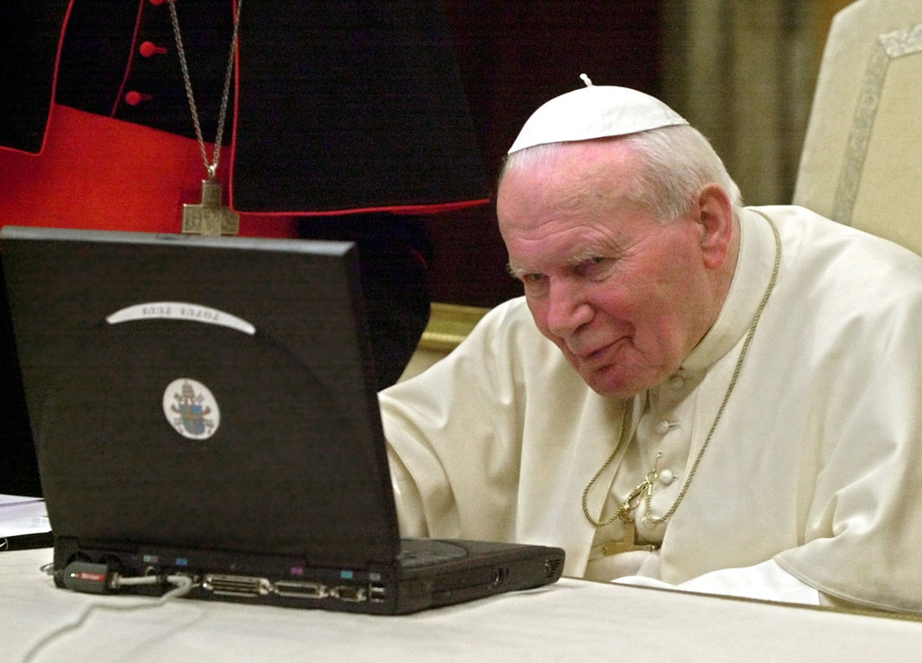 Description of . Pope John Paul II uses a computer to send a special message to bishops in Oceania via Internet during an audience in the Clementine hall at the Vatican in this Nov. 22, 2001 file photo. He presides over an ancient organization with two  millennia of history, but Pope John Paul II is like anyone who's been away from the office for a while: His e-mail is piling up. The Vatican says it's logged more than 10,000 e-mails in English alone for the pope, who is recovering at a Rome hospital from throat surgery to ease his second breathing crisis in a month. (AP Photo/Massimo Sambucetti)
