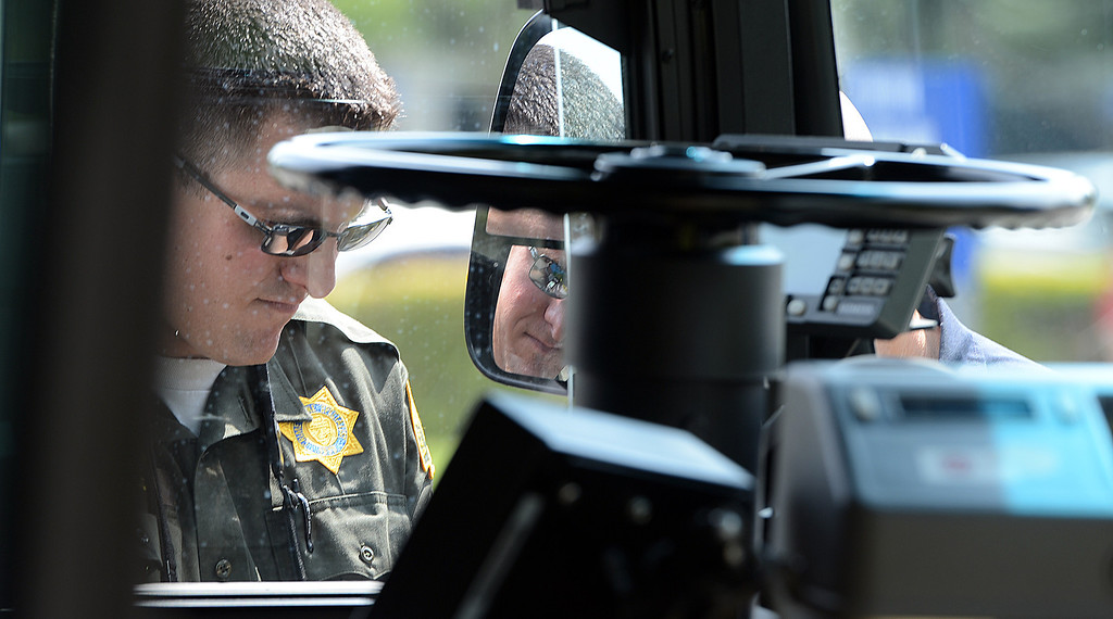 Description of . Mike Russ, a San Bernardino Sheriff's crime scene investigator, looks over an OmniTrans bus that was struck by gunfire during an officer involved shooting in San Bernardino May 9, 2013. Two suspects in a Yucca Valley homicide led authorities on a high-speed chase Thursday that ended with a gun battle, one suspect dead, another wounded and a California Highway Patrol officer wounded. The CHP didn't say where the bullet struck the officer, but said the wound was not life-threatening. (Rick Sforza/The Sun, San Bernardino)