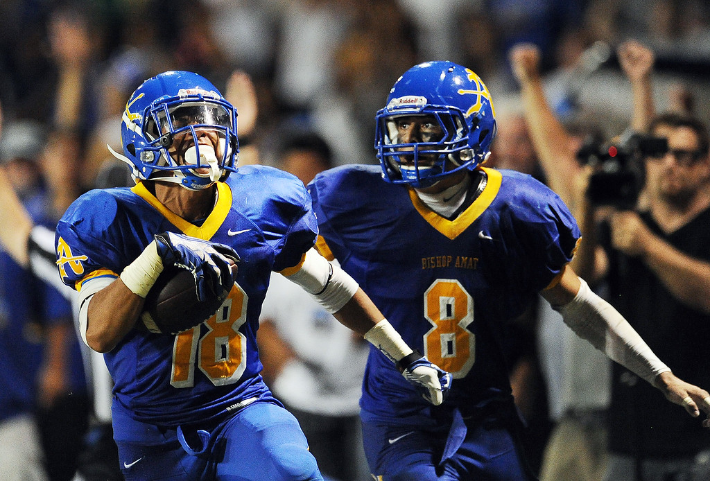 Description of . Bishop Amat's Trevon Sidney (18) recovers a Santa Margarita fumble and runs back for a touchdown as teammate Michael Gonzales (8) looks on in the second half of a prep football game at Bishop Amat High School on Friday, Aug. 30, 2013 in La Puente, Calif. Bishop Amat won 38-28.   (Keith Birmingham/Pasadena Star-News)