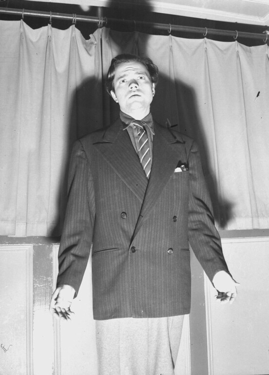 Description of . Orson Welles is shown putting out his hands after his CBS radio broadcast over a national hookup October 30, 1938, which dramatized an H.G. Wells novel called
