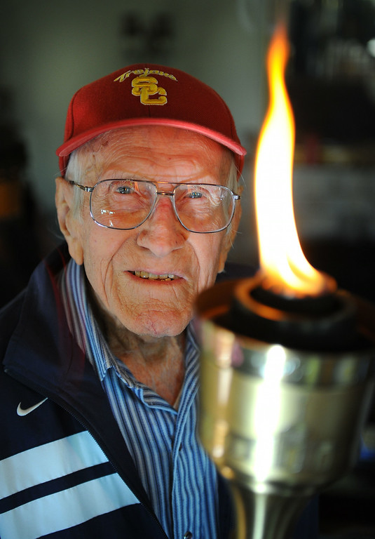 Description of . Louis Zamperini, 94, at his Hollywood home. The flame still burns in him as he holds the olympic torch he carried at the 1984 Olympic Games. (Photo by Brad Graverson/Daily Breeze) 11-7-10