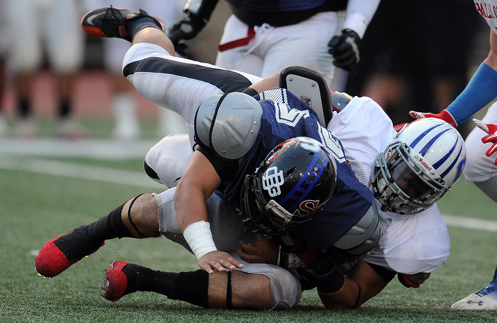 Description of . East's Eric Ortiz (Charter Oak) tackles West's Roger Lemus (24) (Lincoln) for a loss of yards in the first half of the annual East vs. West San Gabriel Valley Hall of Fame all-star football game at West Covina High School on Friday, May 17, 2013 in West Covina, Calif. 
