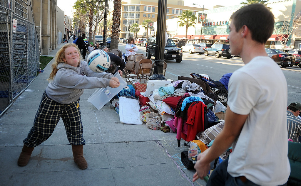 Description of . Sara Ebersole, left, of Napa Valley plays volleyball with Arnaud Caldow of Belgium as they camp out and stake their spots for the Rose Parade along Colorado Boulevard in Pasadena, Calif., on Tuesday, Dec. 29, 2013.     (Keith Birmingham Pasadena Star-News)