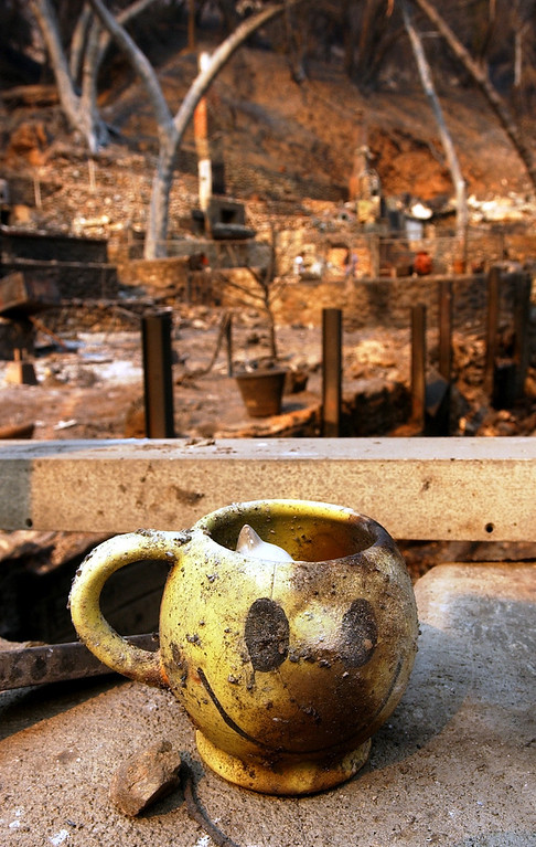 Description of . The GrandPrix fire started three days before the Old Fire.  It fed into the Old Fire. Ten years later, there are rumblings that it too was started by an arsonist. But to this day, its origins remain a mystery. Debbie Dey's scorched coffee mug sits among the ruins of her burned down home in Palmer Canyon, Tuesday, Oct. 28, 2003, in Claremont. (Staff photo by Will Lester/Inland Valley Daily Bulletin)