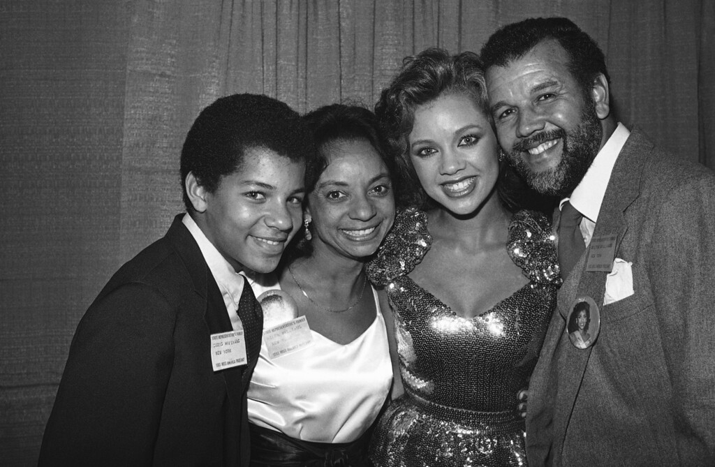 Description of . Shown with her family, Saturday, Sept. 17, 1983 at the Miss America Pageant in Atlantic City is Vanessa Williams, Miss New York. With her is 15-year-old brother, Christopher, mother Helen, and father Milton. Miss Williams is the first black woman to become a double preliminary winner in the Pageant and is considered a top contender to become the first black Miss America. (AP Photo/Jack Kanthal)