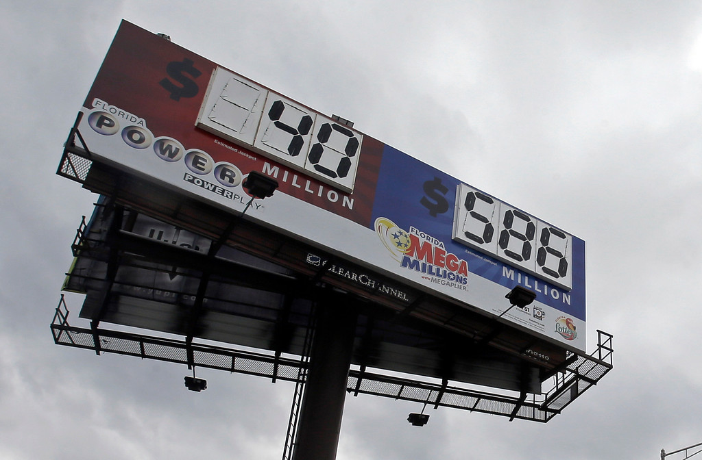 Description of . A billboard shows the jackpot for Powerball and the Mega Millions prize-winning tickets Monday, Dec. 16, 2013, in Hialeah, Fla. The Mega Millions jackpot soared to $586 million on Monday amid a frenzy of ticket purchases, a jump that pushed the prize closer to the $656 million U.S. record set last year. (AP Photo/Alan Diaz)
