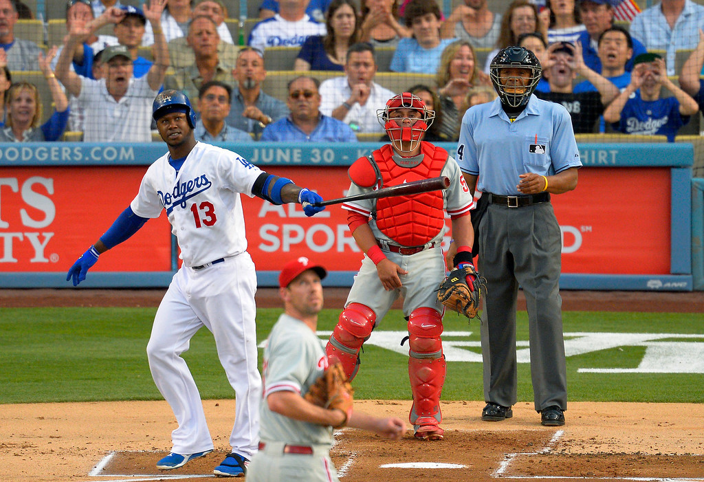 Description of . Los Angeles Dodgers' Hanley Ramirez, left, hits a three-run home run as Philadelphia Phillies starting pitcher Cliff Lee, second from left, looks on along with catcher Carlos Ruiz, second from right, and home plate umpire CB Bucknor during the first inning of their baseball game, Saturday, June 29, 2013, in Los Angeles.   Dodgers won 4-3.   (AP Photo/Mark J. Terrill)