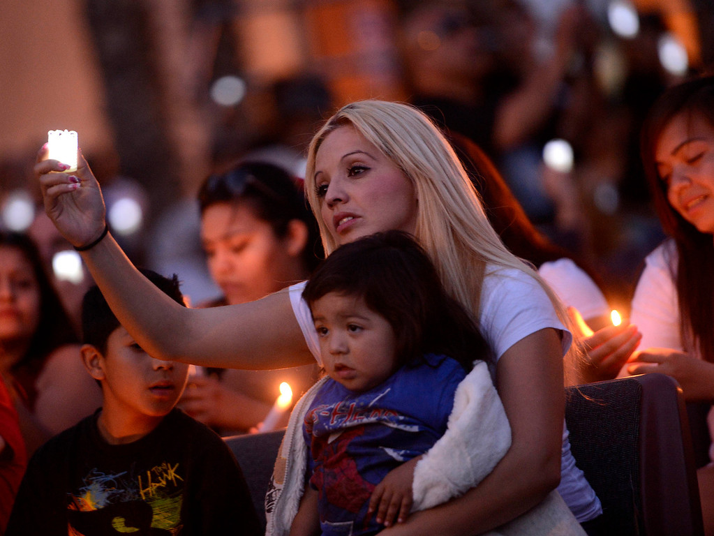 Description of . Alma Espinoza with son Isaac, 1, commemorate the life of her nephew Robert Elizarraraz during the annual Victims Candlelight Vigil at the police station in San Bernardino April 23, 2013.    Elizarraraz died February of 2012 as a victim of violence.  (Photo by Gabriel Luis Acosta/The Sun)