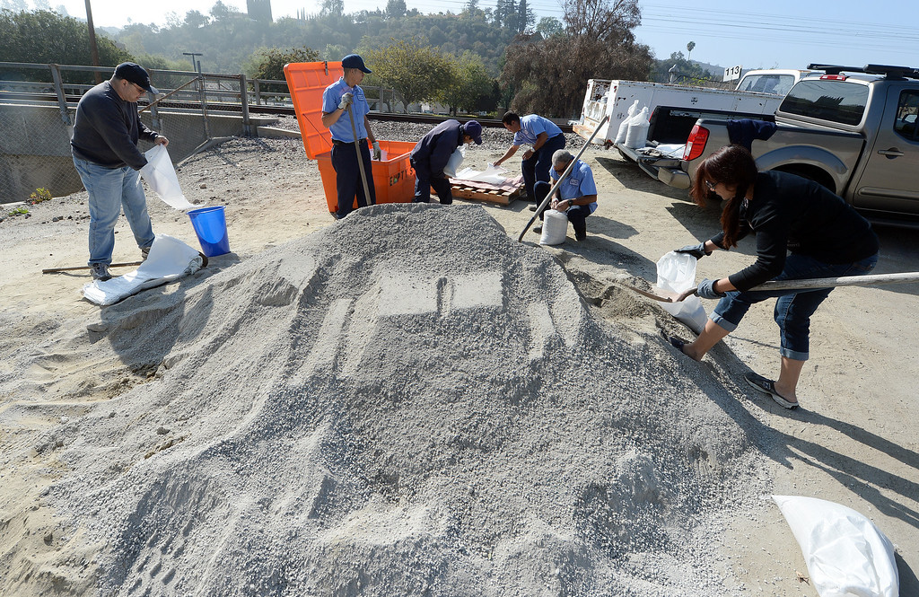 Description of . Glendora residents fill sand bags at the city yard Tuesday February 25, 2014 while public works crews place concrete barriers to divert possible water and flood flows on Sierra Madre Aveune, Brown Sage Drive and Leose Lane. Possible heavy rains in the coming days could create mud flows off of the burned hill sides caused by January's Colby Fire. (Will Lester/Inland Valley Daily Bulletin)
