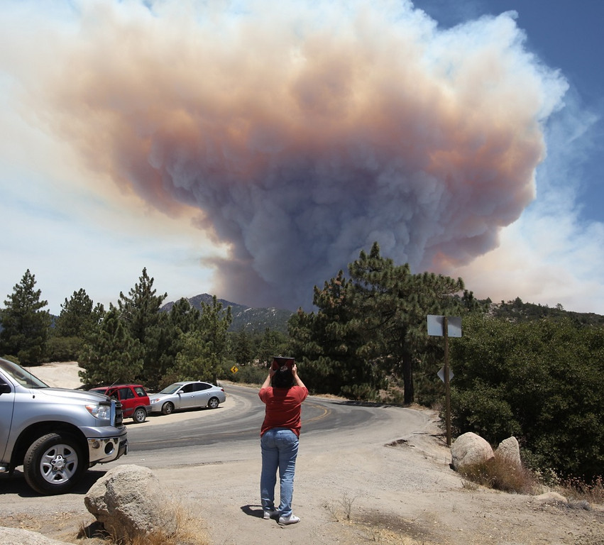 Description of . Onlookers stop and take pictures of a large mushroom cloud of smoke coming from the Mountain Fire near Idyllwild, Calif., Wednesday, July 17, 2013. Authorities asked for additional evacuations as the wildfire in the mountains southwest of Palm Springs rages on. (AP Photo/The Desert Sun, Richard Lui)