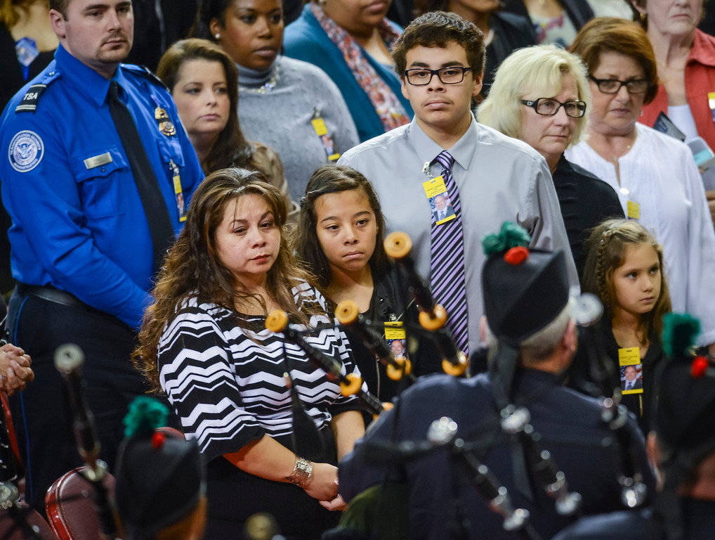 Description of . Ana Hernandez, with children Stephanie and Luis watch look on as the Sheriff bagpipers play at the memorial for their husband and father, Gerardo Hernandez at the Los Angeles Sports Arena Tuesday, November 12, 2013.  A public memorial was held for Officer Hernandez who was killed at LAX when a gunman entered terminal 3 and opened fire with a semi-automatic rifle.  ( Photo by David Crane/Los Angeles Daily News )