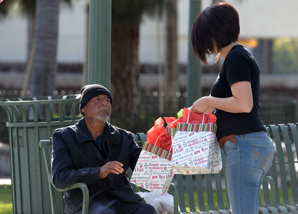 Description of . Jessica Zuniga, right, hands out a gift bag to a homeless man at the Whittier transportation Center in Whittier, Calif., on Saturday, Jan.4, 2014. Zuniga was given a large sum of money by an unidentified man at Target when he thought she had no money.   (Keith Birmingham Pasadena Star-News)
