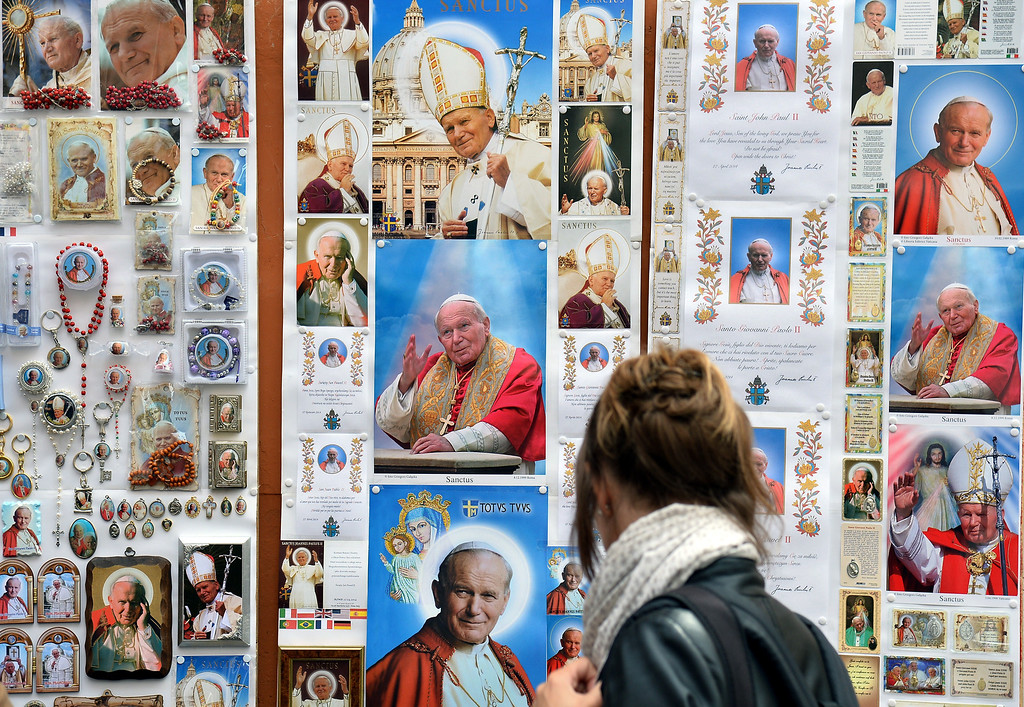 Description of . A woman looks at images of Pope John Paul II, that will be canonized next Sunday, during the Pope Francis' weekly general audience on April 23, 2014.                (ALBERTO PIZZOLI/AFP/Getty Images)