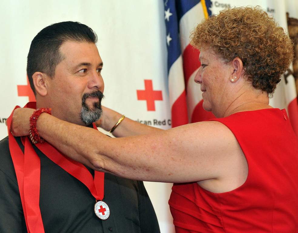 Description of . John Lujan, of Whittier, receives a medal from Mollie Beck as the Rio Hondo Chapter of the American Red Cross honors 14 people for their part in performing extraordinary acts during their Hometown Heroes luncheon at the Quiet Cannon in Montebello on Thursday June 27, 2013. (SGVN/Staff Photo by Keith Durflinger)