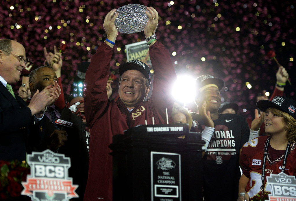 Description of . Florida State head coach Jimbo Fisher holds-up the championship trophy after defeating Auburn 34-31 during the BCS National Championship game at the Rose Bowl in Pasadena, Calif., on Monday, Jan. 6, 2014.  (Keith Birmingham Pasadena Star-News)